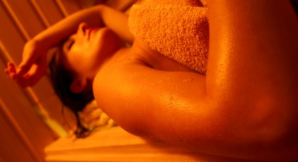 woman laying down in sauna in orange light