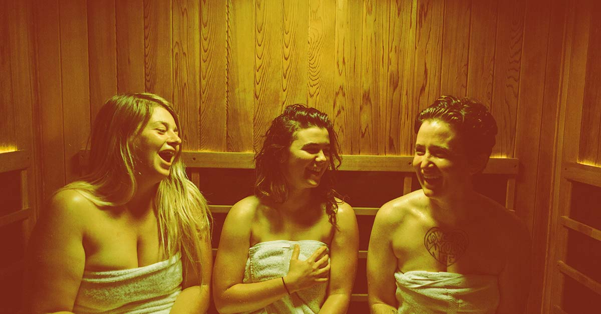 Friends detoxing in a private sauna using yellow light therapy