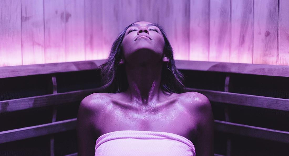 Woman in Perspire Sauna Studio Purple Color light therapy Sauna