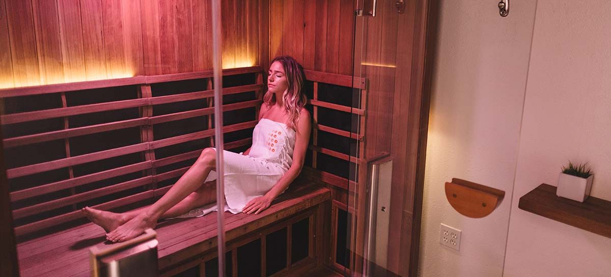 woman sweating out toxins in infrared sauna
