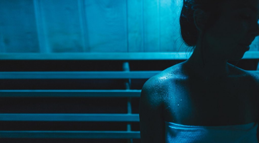 woman sitting in blue light therapy sauna