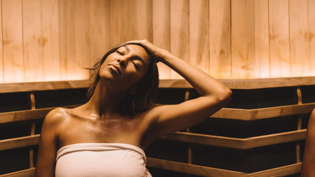 woman stretching her neck in yellow light therapy sauna