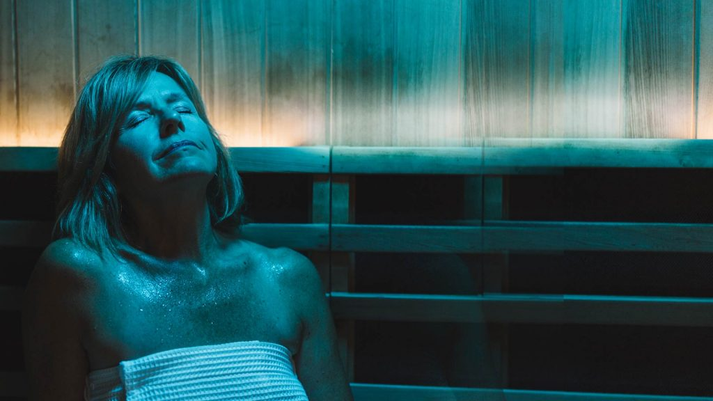 Woman relaxing and smiling in perspire infrared sauna studio