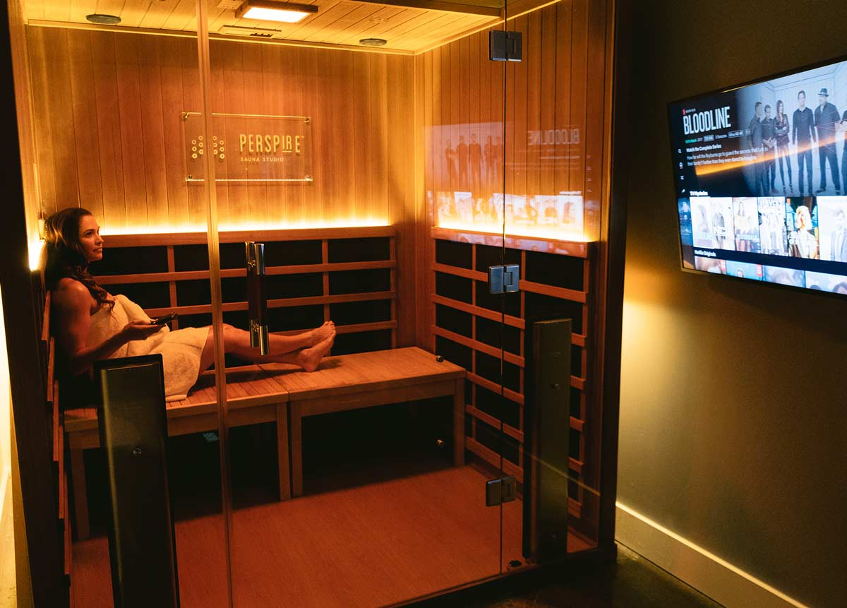 Woman watching tv in a private infrared sauna