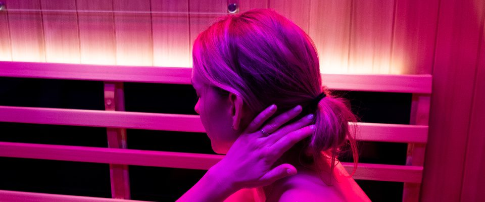 Woman stretching in sauna using color light therapy